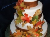 a fall wedding cake with brown ribbons, bright sugar leaves and acorns is a traditional way to embrace the season