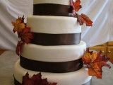 a simple white fall wedding cake with chocolate brown ribbons and dried leaf decor