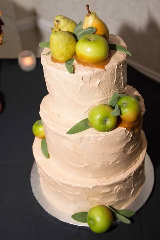 a textural buttercream wedding cake in blush, with pears and apples attached to the cake with caramel