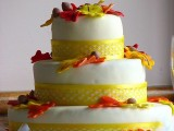 a bright fall wedding cake with neon yellow ribbon, sugar leaves and acorns for a bold look