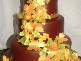 a chocolate wedding cake topped with bright sugar leaves and pumpkins is a statement idea