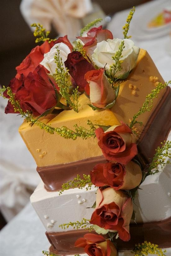 a square white and orange wedding cake with chocolate ribbons and greenery and bold fall blooms