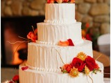 a textural white buttercream wedding cake with branches and bold fall blooms for decor