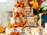 a white wedding cake with chocolate patterns and bold orange blooms for decor