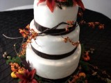 a fall wedding cake decorated with brown ribbons and bold fresh fall blooms and berries