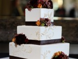 a chic square fall wedding cake decorated with brown ribbons and moody fall blooms plus white patterns