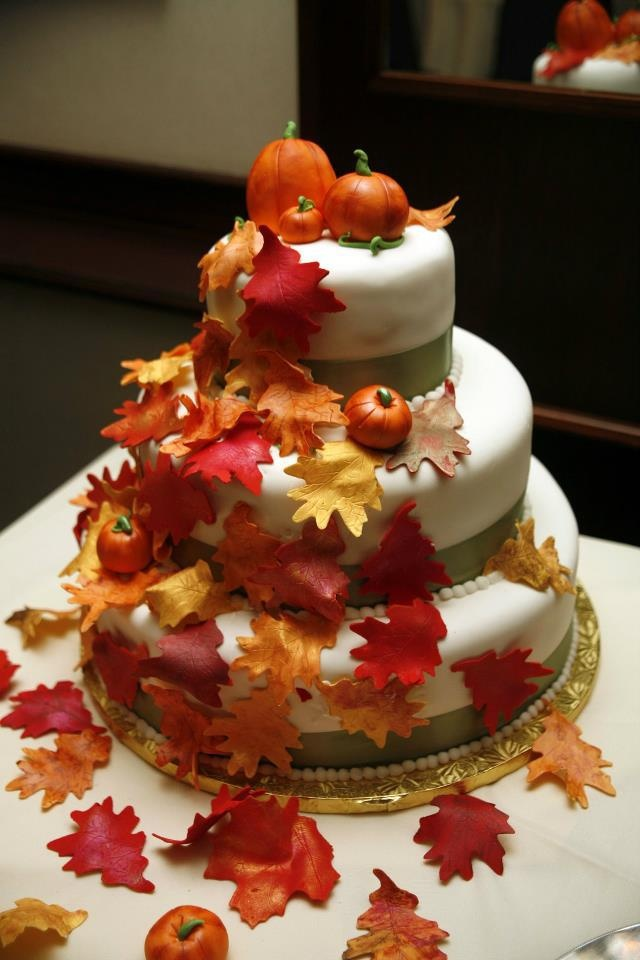 a gorgeous fall wedding cake with green ribbons and sugar leaves and pumpkins