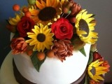 a fall wedding cake with brown ribbons and bold fall sugar blooms on top