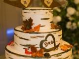 a creative birch bark wedding cake with sugar leaves, acorns, cork bird toppers for a rustic fall wedding
