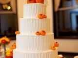 a textural white buttercream wedding cake with sugar pumpkins is a fun and whimsical idea