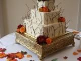 a square fall wedding cake with twigs and bright fall blooms is a creative and chic idea