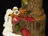 a tree stump wedding cake decorated with sugar leaves and blooms is a very cool idea for a rustic wedding