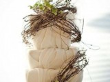a textural neutral wedding cake decorated with vine and greenery looks unique and bold