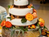 a creative fall wedding cake decorated with chocolate ribbons, bright fall blooms and berries
