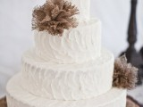 a white textural buttercream wedding cake decorated with burlap balls is ideal for a rustic fall wedding