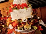 a very creative fall wedding cake that looks like a square caked with leaves and blooms placed on a wooden basket with apples and pears