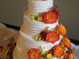 a textural white buttercream wedding cake decorated with greenery and bright fall blooms