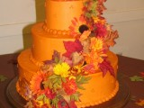 an orange wedding cake decorated with sugar leaves and blooms is a colorful idea for a fall wedding