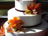 a white fall wedding cake topped with fall leaves and berries is a gorgeous idea with a natural touch