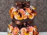 a chocolate fall wedding cake decorated with fresh fall blooms and baby's breath for a bold contrast
