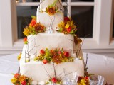 a white square wedding cake decorated with twigs, berries and bright fall blooms looks pretty natural
