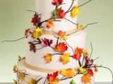 a white fall wedding cake with ribbons, twigs and bright fall blooms for a bold contrasting look