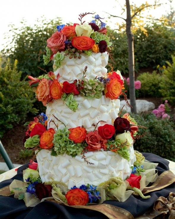a white chocolate wedding cake decorated fresh blooms in fall colors looks really unusual