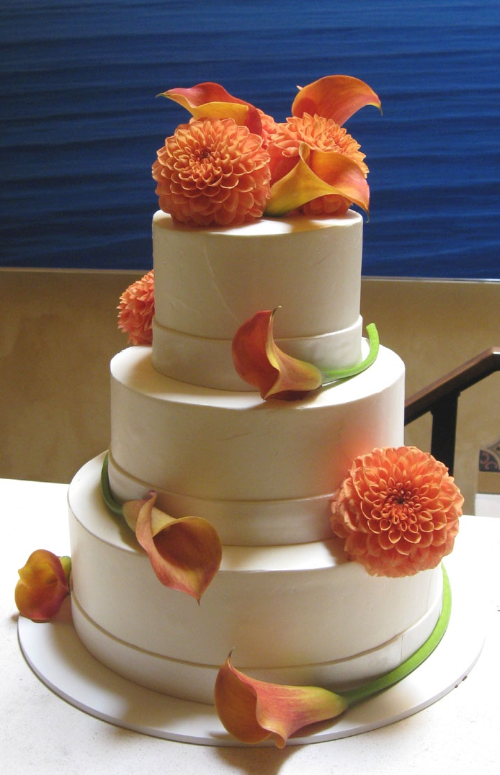 a white fall wedding cake decorated with orange blooms looks and feels fall like
