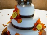 a fall wedding cake with brown ribbons, fall leaves and funny squirrel toppers