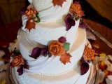 a white wedding cake with sugar beads and ribbons and bright sugar blooms and leaves