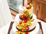 a white wedding cake with brown ribbons, apples, twigs and sugar leaves for the fall
