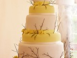 a yellow and white fall wedding cake decorated with twigs and yellow blooms plus a nest with branches