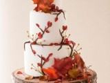 a fall wedding cake with sugar blooms, twigs and berries in bold colors for a bright fall wedding