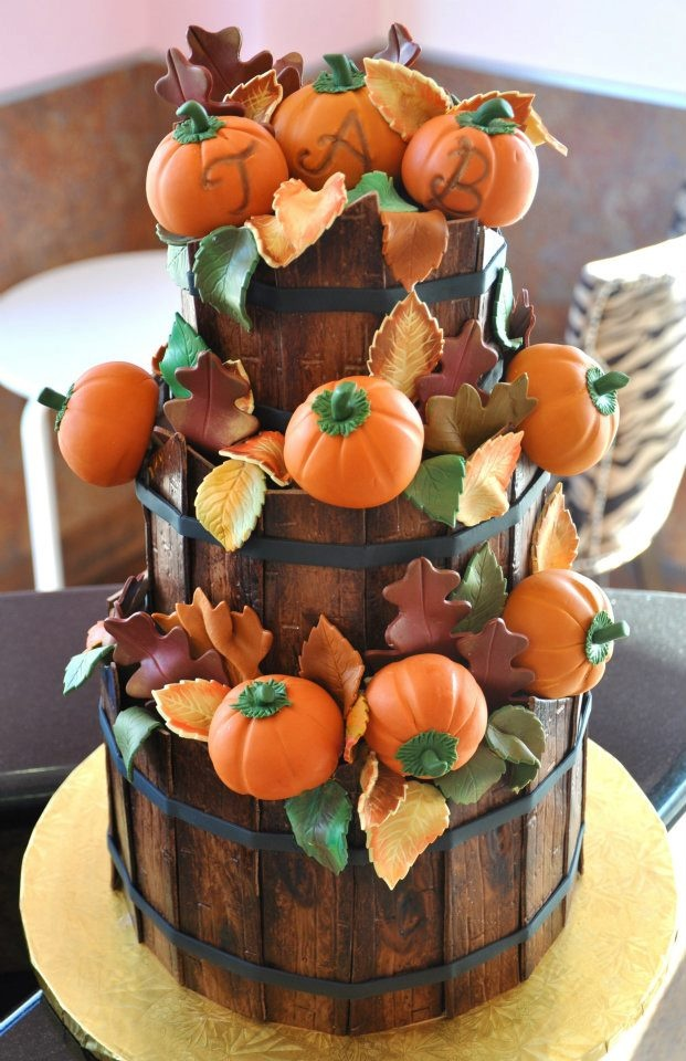 a creative fall wedding cake showing off wooden baskets filled with leaves and sugar pumpkins