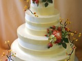 a striped neutral fall wedding cake decorated with sugar blooms, leaves and berries