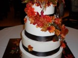 a dramatic white wedidng cake decorated with dark ribbons and bright fall-colored blooms and leaves