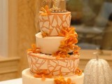 a fall wedding cake with shards, bright ornage blooms and a shiny embellished tree topper for the fall
