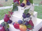 a white square wedding cake topped with fresh fall fruit and foliage looks super cool and yummy