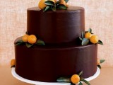 a chocolate wedding cake decorated with leaves and citrus is great for the fall