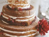 a naked wedding cake with bright fall blooms, acorns and lush neutral flowers on the top
