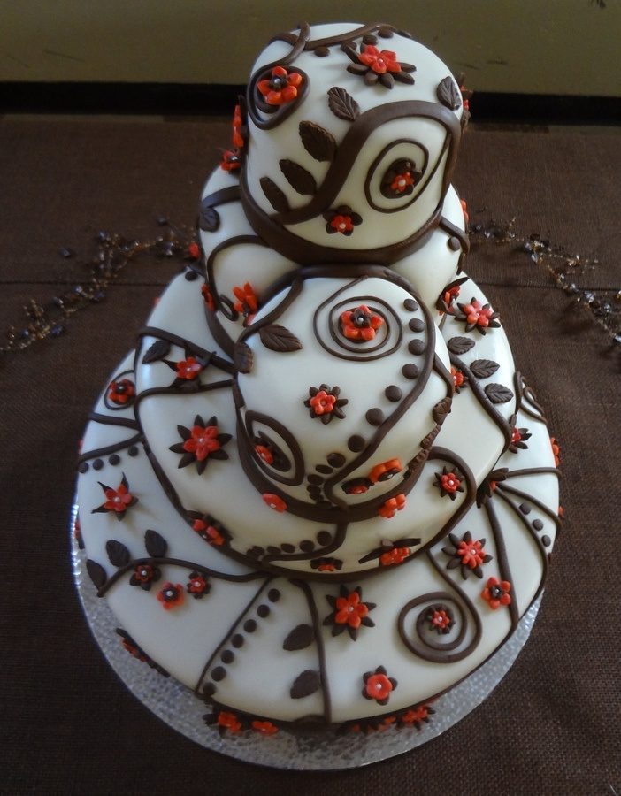 a unique buttercream wedding cake decorated with chocolate and orange patterns all over looks very bold