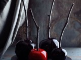 candied red and deep purple apples on sticks are delicious Halloween wedding favors that your guests may enjoy