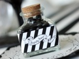 a bottle with black candies and a striped sticker is a cool and creative Halloween wedding favor idea to make yourself