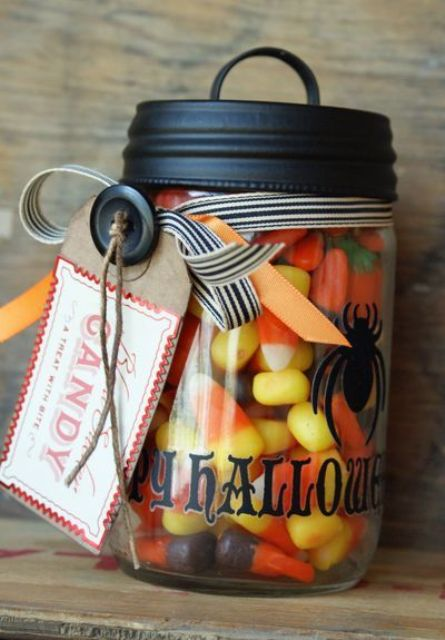 a jar with colorful Halloween candies with a striped strap and tags is a stylish and fun Halloween wedding favor