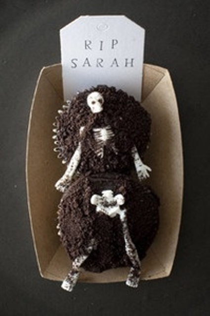 a box with two cupcakes as a grave and a skeleton on top is a creative and unusual Halloween wedding favor