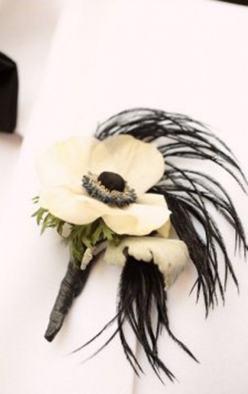 a white bloom boutonniere with black feathers and greenery