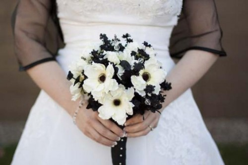 a white wedding dress, a black sheer coverup and a black and white wedding bouquet