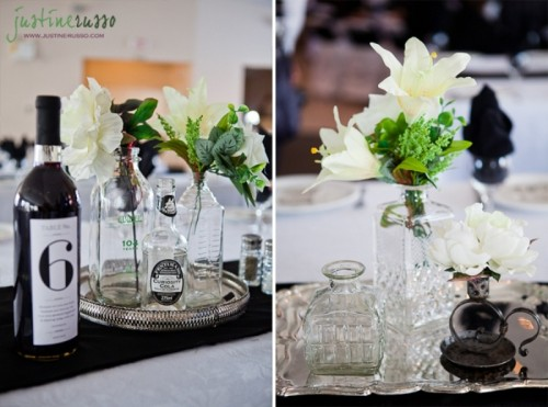 a wedding tablescape with neutral bottles with greenery and blooms and a wine bottle with a black table number