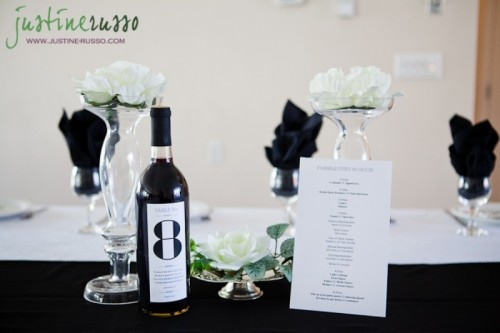 clear glass vases with white blooms, white table runners and napkins plus a table number