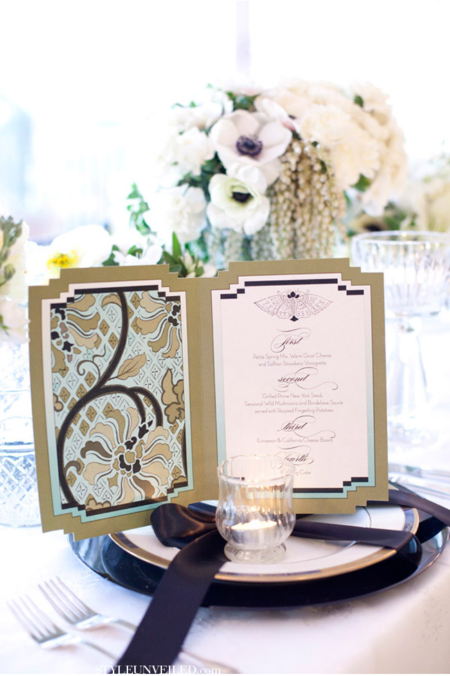a black and white place setting and a menu in black, white and gold